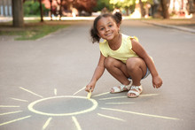Little African-American Child Drawing Sun With Chalk On Asphalt