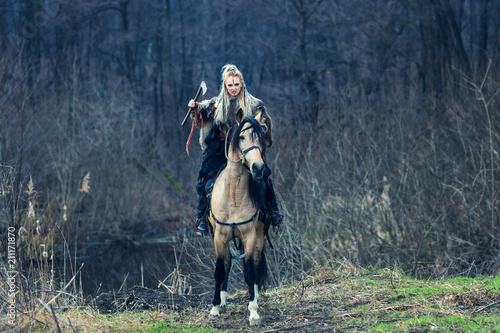 Photo  Scandinavian northern viking riding horse with ax in hand