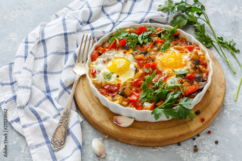 Spicy shakshuka with eggs, eggplant and tomatoes.
