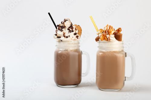 Staande foto Milkshake Mason jars with delicious milk shakes on white background