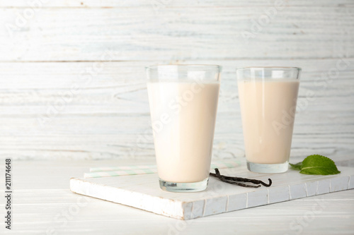 Spoed Foto op Canvas Milkshake Glasses with vanilla milk shakes on table