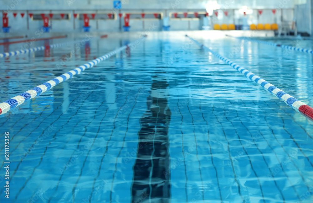 Fototapeta Modern swimming pool with blue water, indoors