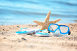 Starfish, goggles and flip flops on sand near sea. Beach object