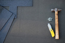 Close Up View On Unfinished Asphalt Roofing Shingles Background With Hammer And Nails. Installation Of Waterproofing Coating In Construction.