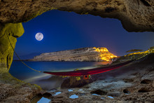 Cave With Hammock At Night With Full Moon, Matala, Crete, Greece.