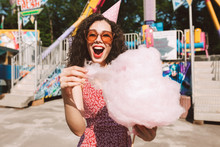 Cheerful Lady With Dark Curly Hair In Sunglasses And Birthday Cap Standing With Cotton Candy In Hand And Happily Looking In Camera While Spending Time In Amusement Park