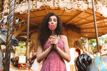 Beautiful Lady With Dark Curly Hair In Dress Standing And Covering Her Mouth With Candy While Dreamily Looking In Camera With Carousel On Background