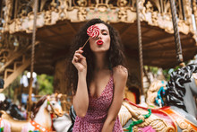 Beautiful Lady With Dark Curly Hair In Dress Standing And Covering Her Eye With Lolly Pop Candy While Dreamily Looking In Camera With Carousel On Background