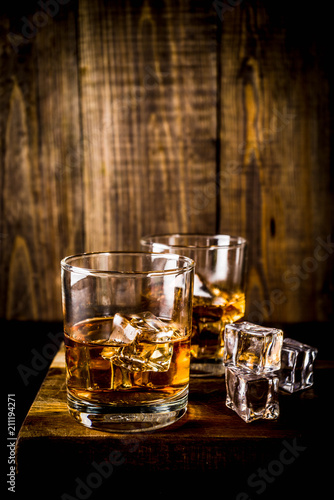 Two whiskey shot glasses on dark wooden background, with ice cubes, copy space Canvas Print
