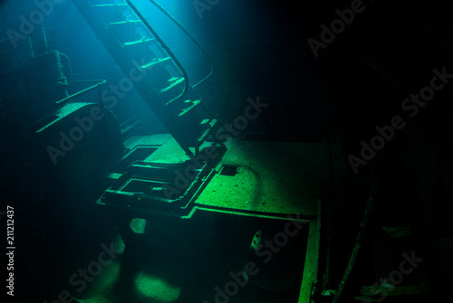 Photo Stands Shipwreck An underwater shot inside a room in the shipwreck of the Kittiwake that uses natural light as opposed to a strobe. The wreck has been sunk deliberately and is shallow enough to allow light penetration