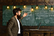 Businessman work on laptop in classroom. Businessman in suit with notebook point at chalkboard, new technology concept