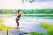 Young woman doing yoga pose beside the lake.