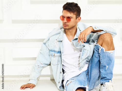 Poster  Portrait of handsome young model man dressed in jeans clothes sitting near white