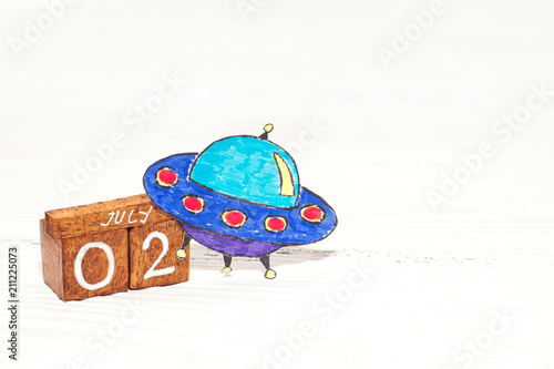 Staande foto UFO Jule 2nd - World UFO Day on wooden calendar with funny picture of UFO