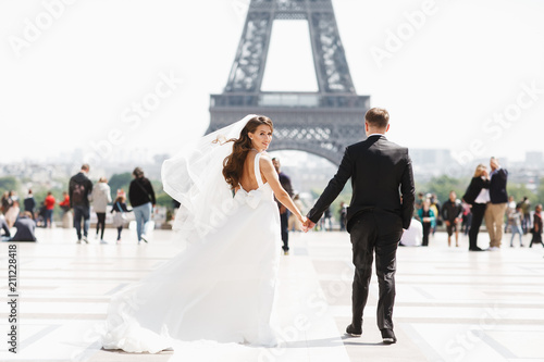 Photo  Beautiful wedding couple has fun posing on the square before the Eiffel Tower in