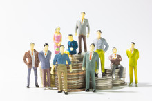 A Group Of Miniature Businessman On Stack Of Coins Closeup.