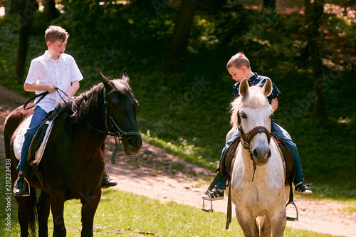 Poster Equitation The twins boys riding on the horses