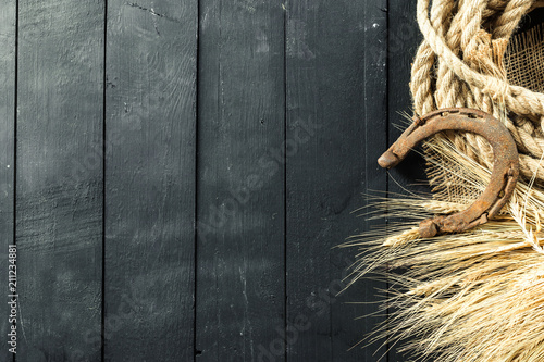 Photo Old horseshoe and rope on wooden boards
