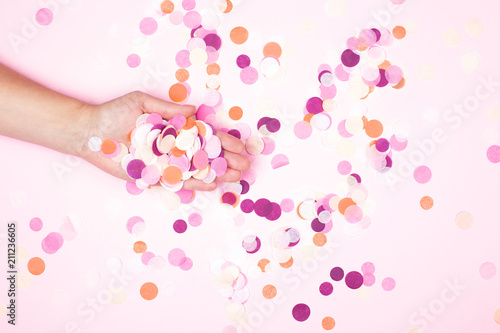 Obraz View from above on hand with pink confetti. Party explosion concept. - fototapety do salonu