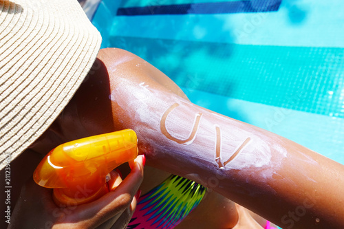 Papiers peints Echelle de hauteur Ultraviolet protection concept with UV text on sunscreen on young woman arm at the swimming pool