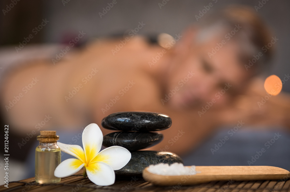 Fototapeta Male spa setting with black hot stones