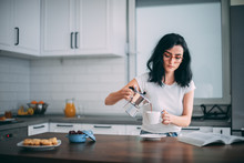 Beautiful Young Woman Pouring Coffee In The Kitchen