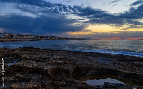 Staande foto Nachtblauw Seascape. Sun in the clouds at sunset over the sea and resort town on the island of Crete