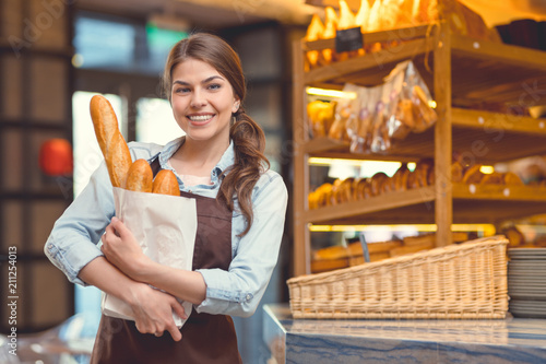 Papiers peints Boulangerie Young woman with baguettes