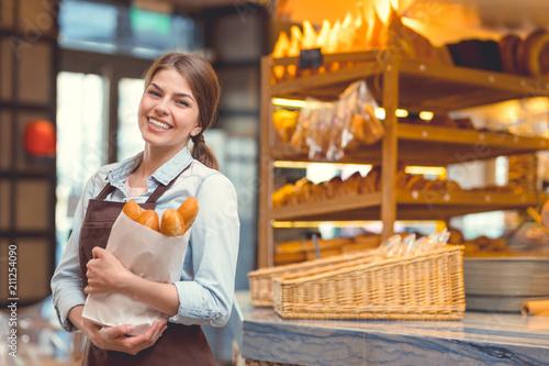 Fototapeta Young baker with baguettes obraz