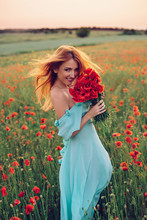 Red-haired Woman With Fluttering Hair Walks Through Flowering Poppy Field