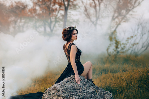 Fotomural The majestic lady, the dark queen, sits on the stone baring her leg