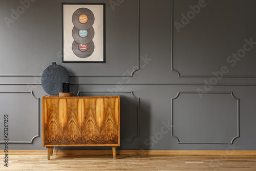 Fotografie, Tablou  Records on grey wall with molding above wooden cabinet in vintage living room interior