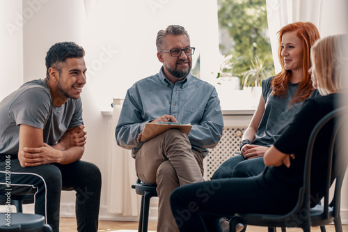 Canvastavla Smiling spanish man talking with friends during meeting for teenagers with thera