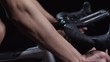 PAN of unrecognizable fit cyclist pedaling bicycle against black background