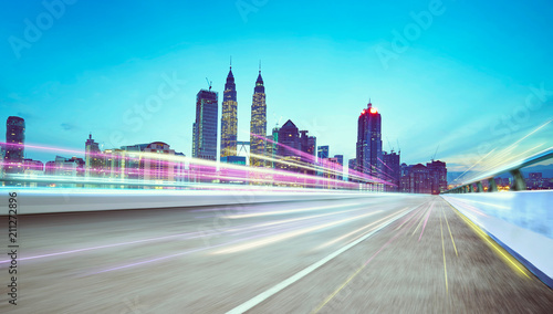 Deurstickers Kuala Lumpur Moving forward motion blur asphalt road on night scene near the modern city with light trail.