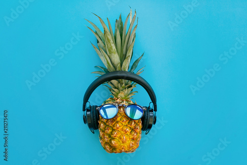 Magasin de musique stylish pineapple in sunglasses and headphones on trendy blue paper background. summer flat lay. vacation and party concept. space for text. hipster holidays
