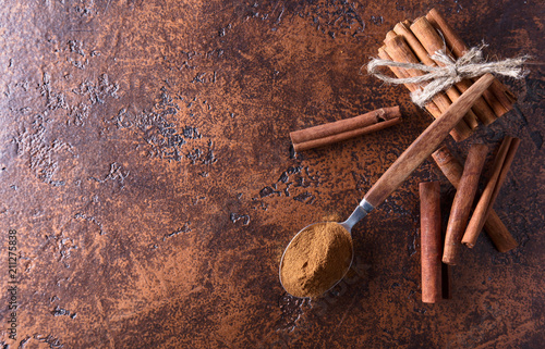 Foto op Canvas Kruiderij Cinnamon sticks and powder in spoon on a old copper table .