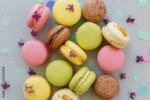 Spoed Foto op Canvas Macarons colorful macarons on trendy pastel gray paper with lilac flowers and confetti, flat lay. tasty pink, yellow, green and brown macaroons. candy bar for party. food photography