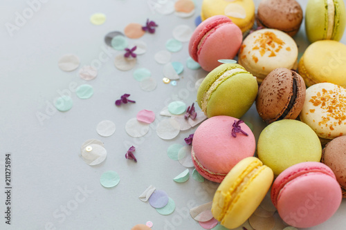 In de dag Macarons colorful macarons on trendy pastel gray paper with lilac flowers and confetti. tasty pink, yellow, green and brown macaroons. candy bar for party. food photography. yummy background