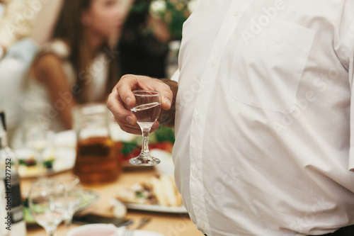 Man Holding Glass Of Vodka And Toasting At Wedding Reception People
