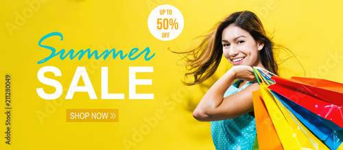 Fototapeta Summer sale with happy young woman holding shopping bags on a yellow background obraz