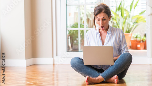 Fotografija  Middle aged woman using laptop at home scared in shock with a surprise face, afr