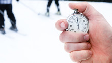 One Person Starting Up A Stopwatch In Hand On A Ski Slope. Man Pushing Timer Button Outdoors. The Second Hand Counts The Time