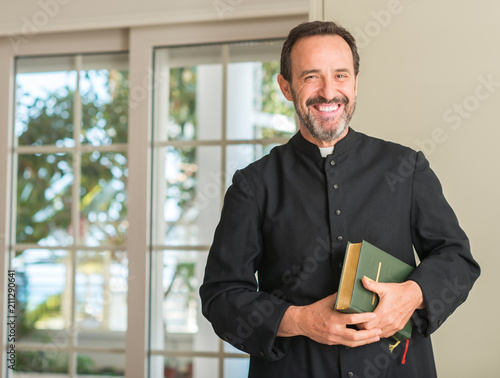Fotografia Christian priest man with a happy face standing and smiling with a confident smi