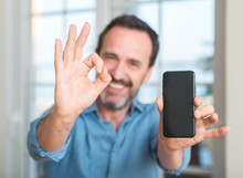 Middle Age Man Using Smartphone Doing Ok Sign With Fingers, Excellent Symbol