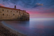 Ancient castle on the beach at sunset with colorful sky reflecting in the water