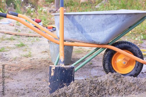 Fotografía  Wheelbarrow and shovel. Construction of the house.