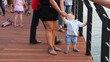 Little, inquisitive boy walks with his mother on the pier