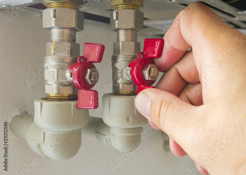 The man opens or closes the hot water valve in the boiler room at home, autonomous heating system фототапет