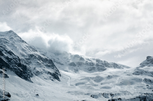 Obraz Gigantic blizzard snow storm clouds casting over the mountain peaks - fototapety do salonu